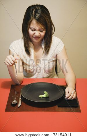 Asian woman with one piece of broccoli on plate