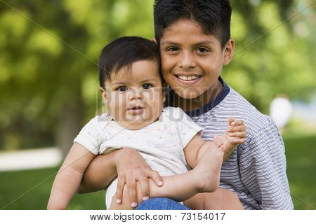 Portrait of Hispanic boy holding baby sibling