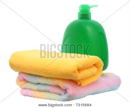 Green Plastic Bottle And Two Towels.