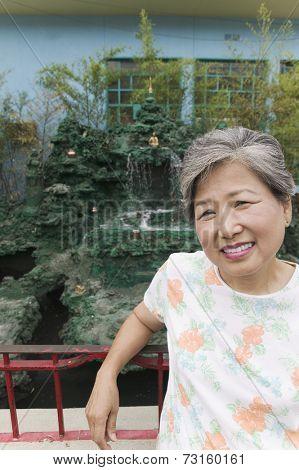 Senior Asian woman leaning against railing