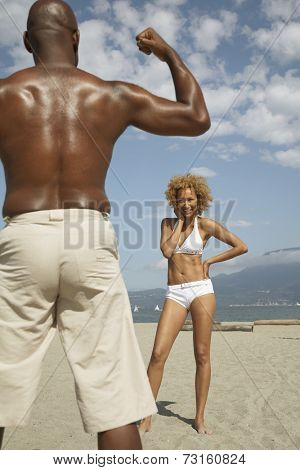 African man flexing for wife at beach