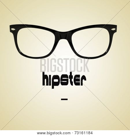 the word hipster and a black plastic rimmed eyeglasses on a beige background with a retro effect