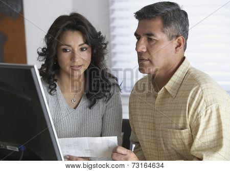 Hispanic couple looking at computer