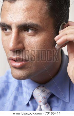 Hispanic businessman wearing hands free device