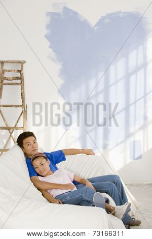 Asian couple in partially painted room