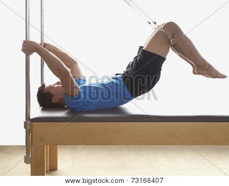 Asian man stretching on exercise equipment