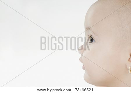 Profile of Hispanic baby with earring
