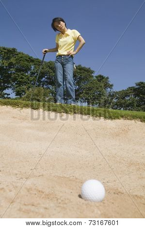 Asian woman looking at golf ball in sand trap
