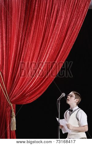 Boy reading from paper on stage