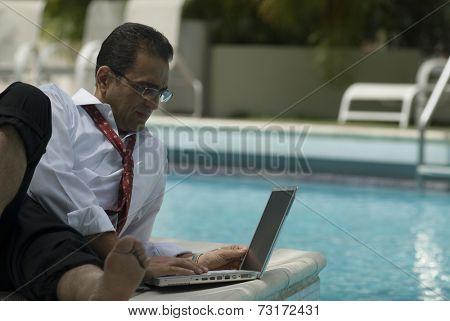 Hispanic businessman using laptop next to swimming pool