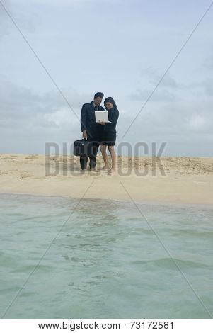 Hispanic businesspeople with laptop at beach