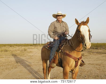 Mixed Race man riding horse