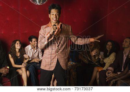 Mixed Race man singing karaoke at nightclub