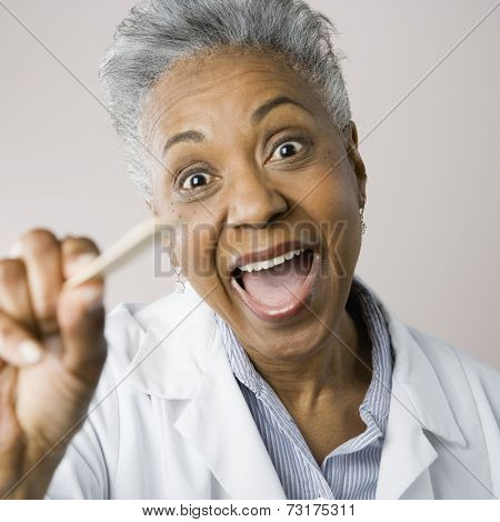 African American female doctor dropping holding tongue depressor