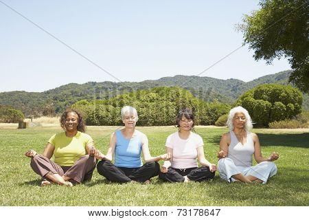 Multi-ethnic senior women meditating