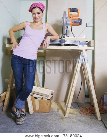 Middle Eastern woman next to table saw