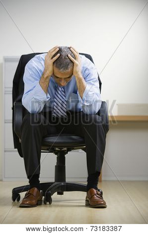 Middle Eastern businessman with head in hands