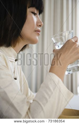 Asian woman holding glass of water