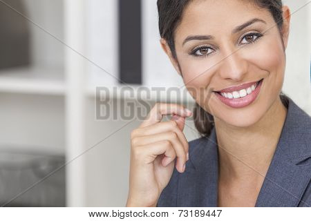 Portrait of a beautiful young Latina Hispanic woman or businesswoman wearing smart business suit in her office