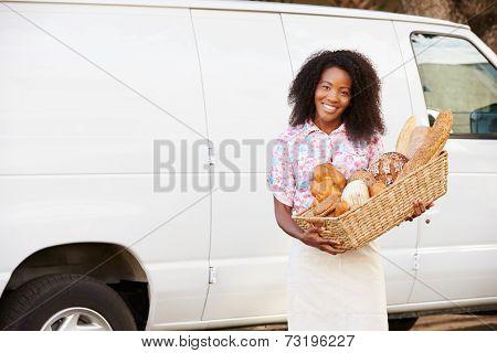 Female Baker Delivering Bread Standing In Front Of Van