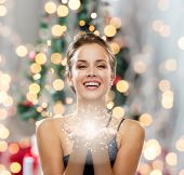 people, holidays and magic concept - laughing woman in evening dress holding something over christmas tree and lights background poster