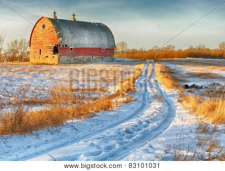 Broken Red Barn and country road on a sunny winter day