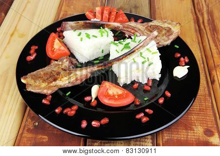 main course: grilled ribs with rice and tomatoes on black dish over wood