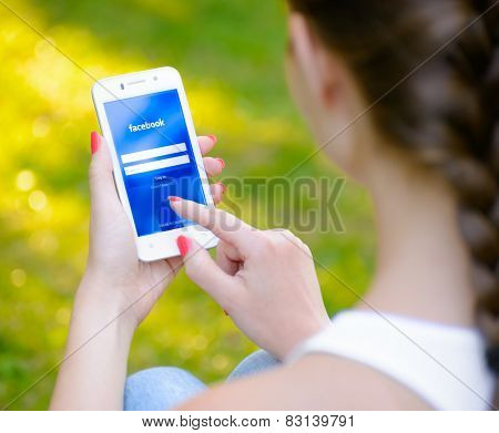 ZAPORIZHZHYA, UKRAINE - SEPTEMBER 20, 2014: Young Woman Using Facebook Social Network Application on her Smart Phone.