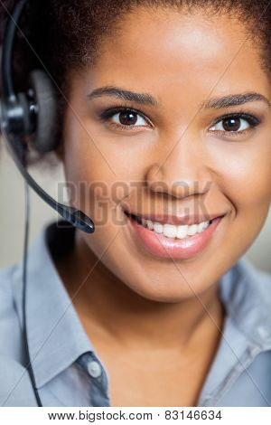 Portrait of young smiling female customer service representative wearing headset in office