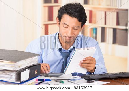 young stressed overwhelmed man with piles of folders on his desk