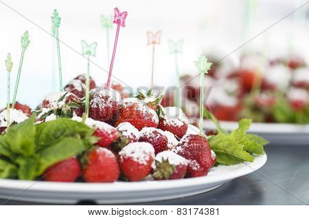 plate of succulent juicy fresh ripe red strawberrie on multicolored plastic food skewers in butterfly and leaf shape decorated with mint