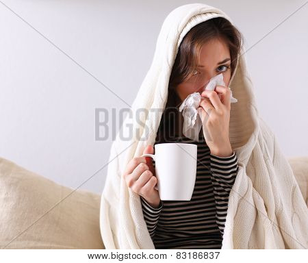 Sick woman covered with blanket holding cup of tea sitting on sofa couch. poster
