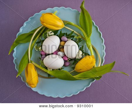An Easter Table Centerpiece Of Colourful Eggs, Tulips And Flowers On A Blue Plate