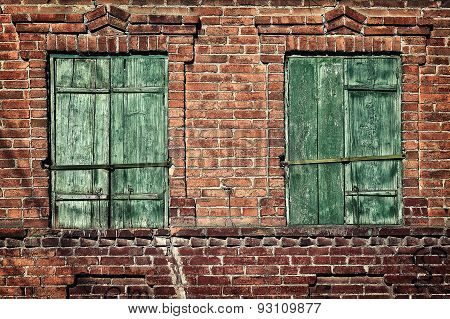 Old Window With Closed Shutters On A Brick Wall