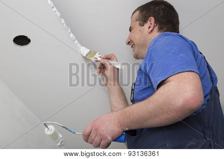 Painter painting a house ceiling with brush and roller