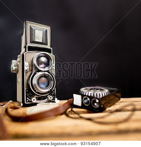 old twin-lens reflex camera with light meter on the black background poster