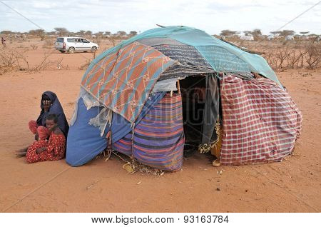 In Refugee Camps, Sitting Next To A Tent With The Child Woman