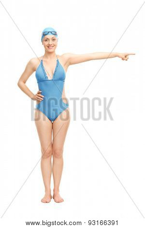 Full length portrait of a female swimmer in a blue swimming costume pointing with her hand isolated on white background