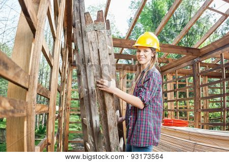Side view portrait of smiling female worker holding ladder in incomplete wooden cabin at site