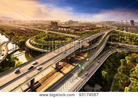 Elevated overpass with skyline of modern city during sunset.