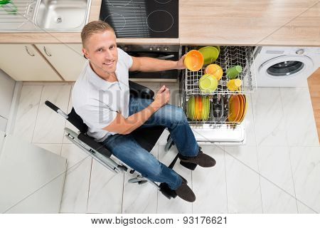 Disabled Man Arranging Plate In Dish Rack