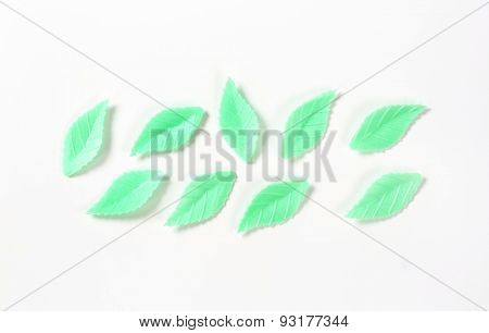 green sugar leaves - eatable cake decoration on white background poster
