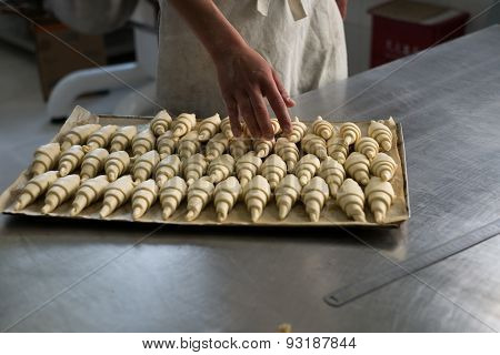 Baker Counting Croissants On A Tray