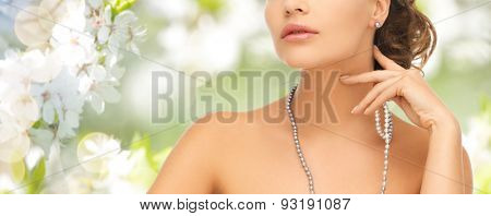 fashion, style, jewelry, beauty and people concept - beautiful woman wearing pearl earrings and necklace over summer garden and cherry blossom background