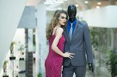 Sexy young girl with bright makeup and curly hair standing with male mannequin in formal clothes on shopping background horizontal picture poster