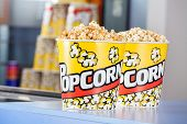 Buckets full of popcorn at concession stand in cinema poster