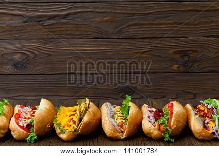 A lot of big delicious hot dogs with sauce and vegetables on wooden background. Their assorted hot dogs to gourmet with copy space for design.