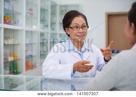 Asian pharmacist talking to customer in drugstore