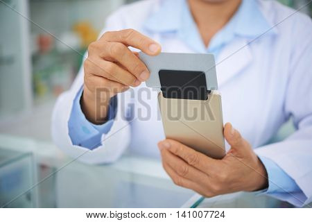 Hands of pharmacist swiping credit card to accept payment