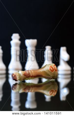 Chess Queen made from Onyx lying before lot of chessmen against dark background